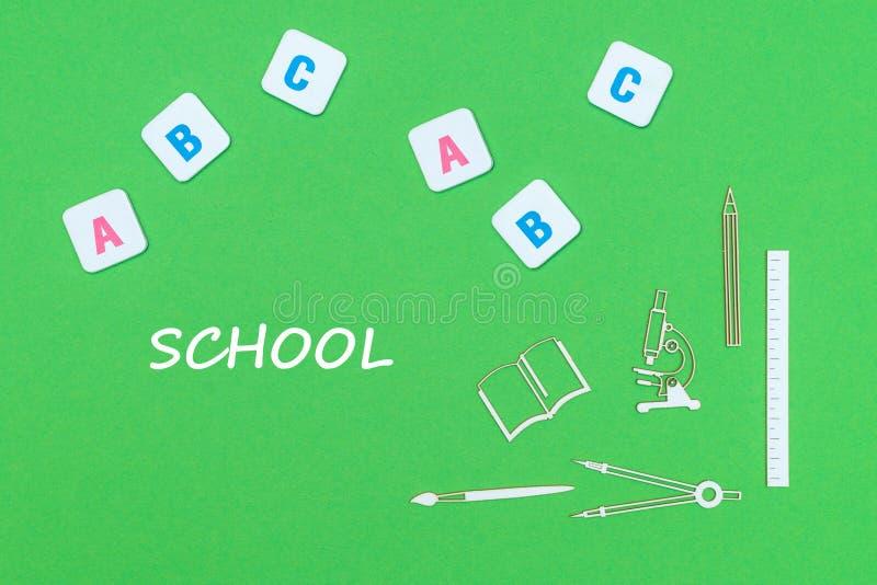 Text a escola, de cima das fontes de escola de madeira dos minitures e das letras do ABC no fundo verde imagem de stock royalty free
