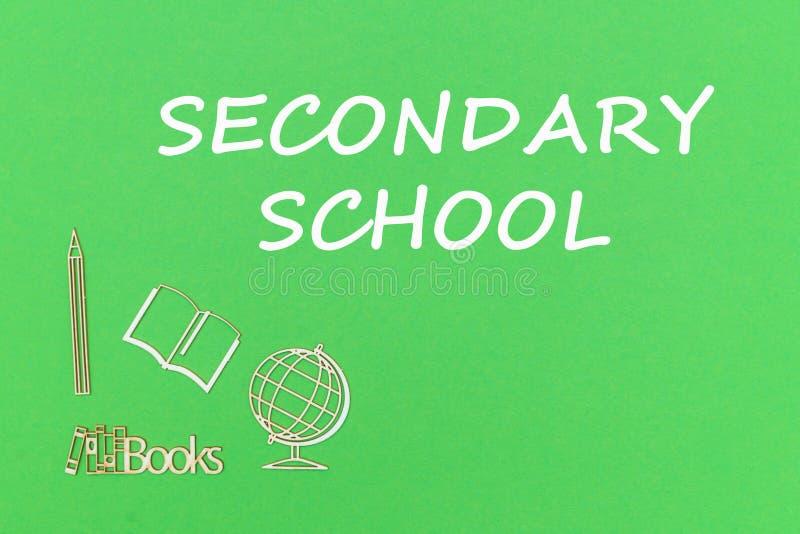 Text a escola secundária, miniaturas de madeira das fontes de escola no fundo verde fotos de stock