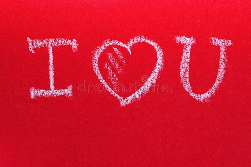 Text eu te amo, escrito pelo giz em uma placa vermelha O dia de Valentim romântico do St do cartão fotos de stock royalty free