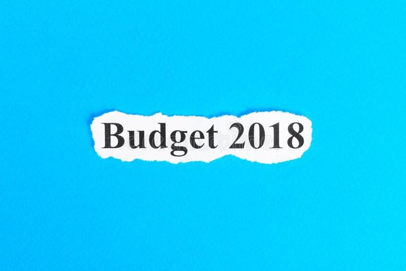 Text för BUDGET 2018 på papper OrdBUDGET 2018 på sönderrivet papper text för rest för bild för com-begreppsfigurine höger plattfo arkivbilder