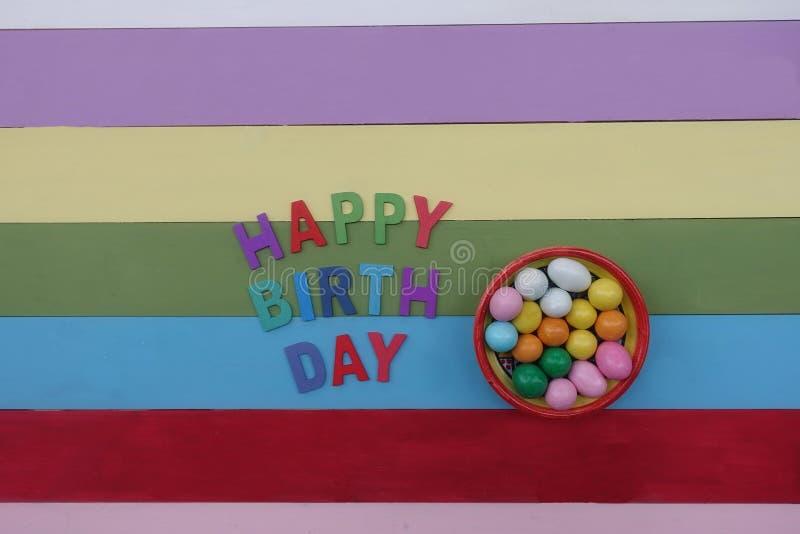 Text för lycklig födelsedag med mång- kulöra träbokstäver och choklader royaltyfria bilder