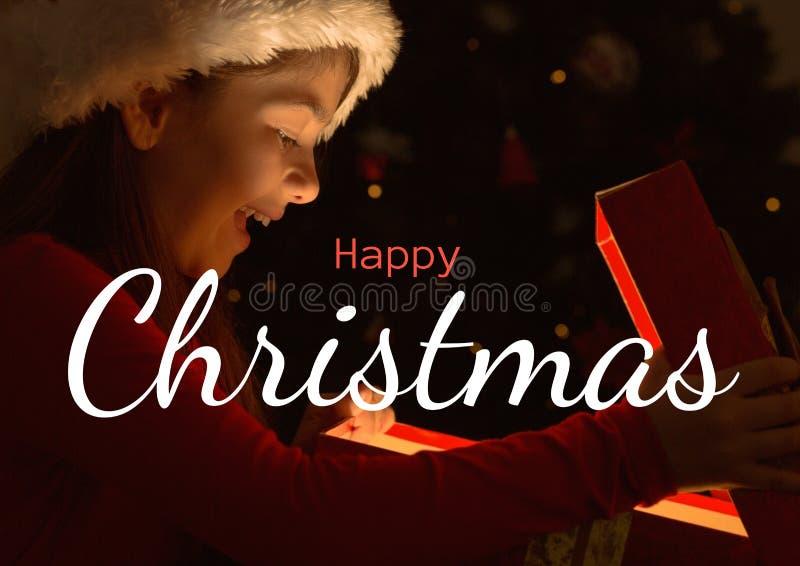 Text för lycklig jul med flickaöppningsgåvan royaltyfri bild