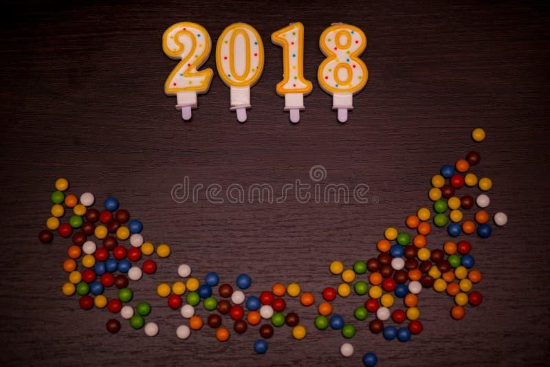 Text för lyckligt nytt år 2018 från stearinljus med färgrikt, godisar på träbakgrund royaltyfri fotografi