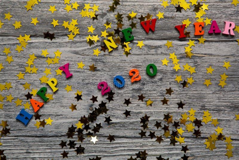 2020 text för lyckligt nytt år för hälsningkort, med guld- stjärnor och kulöra bokstäver på träbakgrund, kalender, inbjudan royaltyfria bilder