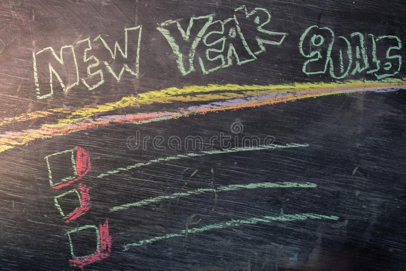 Text för mål för nytt år handskriven med färgrik krita på svart tavlabakgrund royaltyfri foto