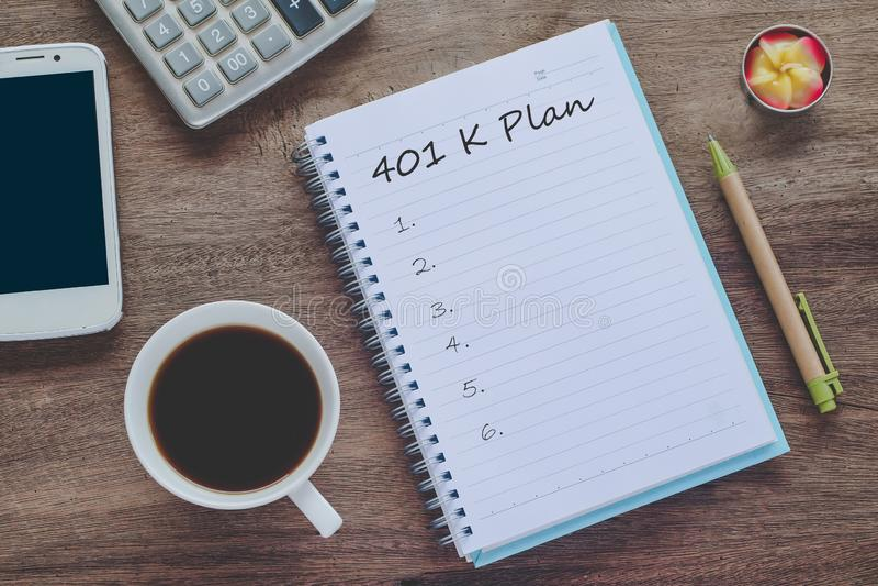 text för plan 401K på bokanmärkning med koppen kaffe, royaltyfria foton