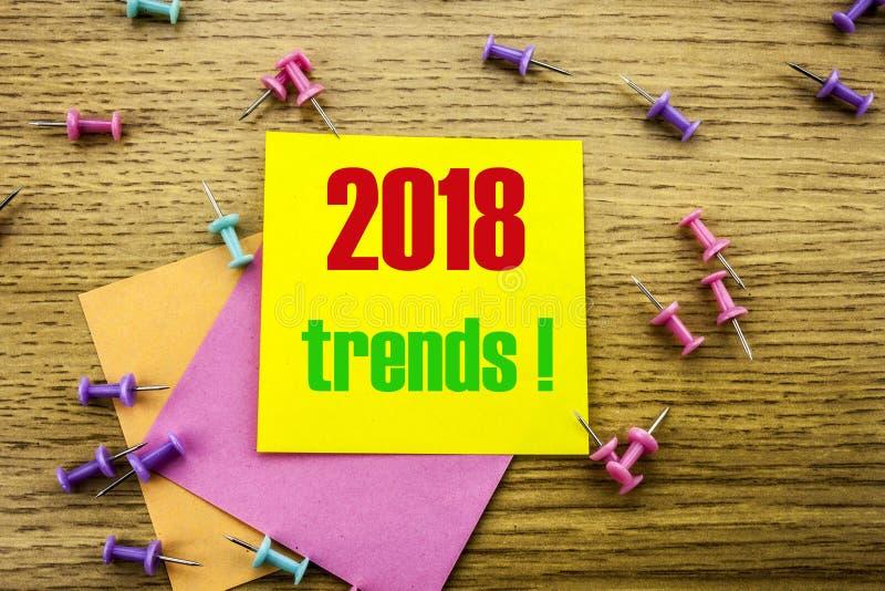 Text för trender 2018 på gul klibbig anmärkning på träbakgrund Minsta begrepp arkivfoto