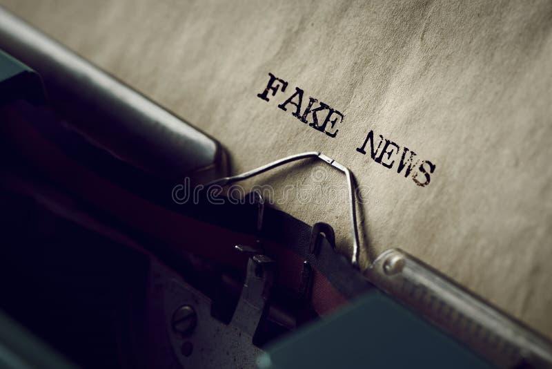 Text fejkar nyheterna som är skriftlig med en skrivmaskin royaltyfri fotografi