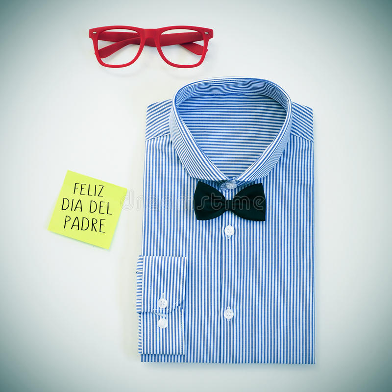 Text feliz dia del padre, happy fathers day in spanish, on a sticky note and some mens stuff. High-angle shot of a table with a pair of eyeglasses, a bow tie and royalty free stock images