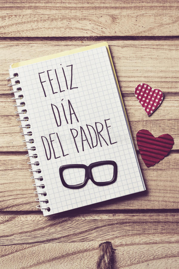Text feliz dia del padre, happy fathers day in Spanish. The text feliz dia del padre, happy fathers day in spanish written in the page of a notebook, a pair of stock photography