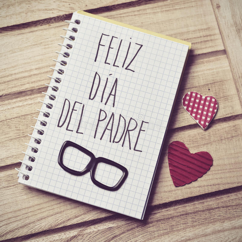 Text feliz dia del padre, happy fathers day in Spanish. The text feliz dia del padre, happy fathers day in spanish written in the page of a notebook, a pair of royalty free stock photos