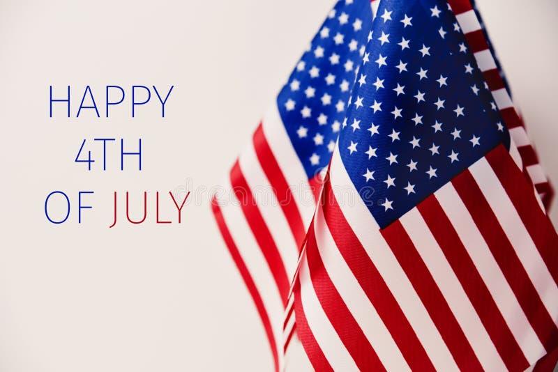 Text feliz 4o julho e bandeiras americanas imagens de stock
