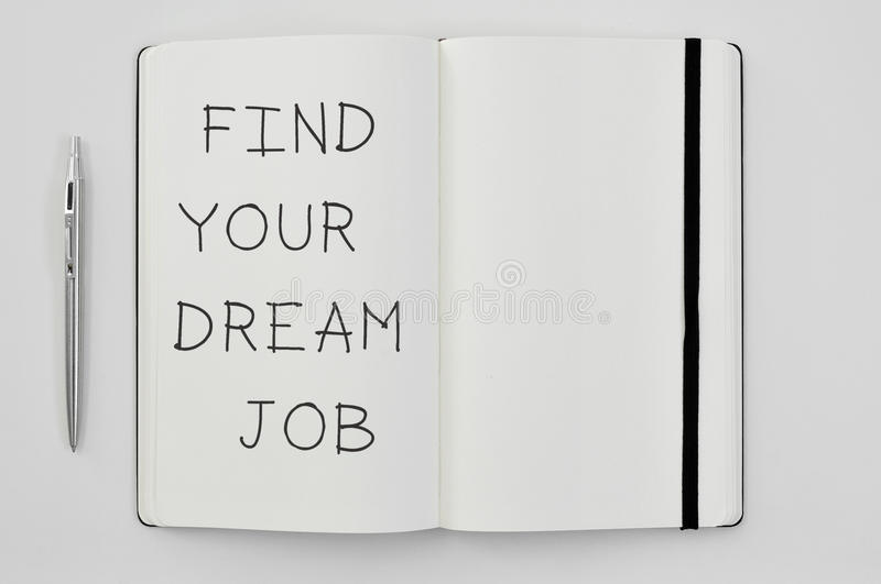 Text find your dream job in a notepad. High-angle shot of a pen and a notepad with the text find your dream job written in it royalty free stock photos