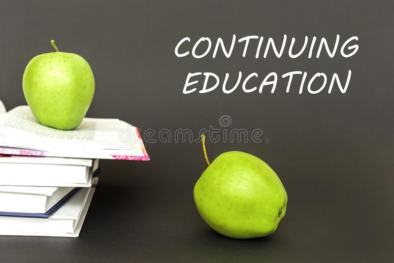 Text a formação permanente, duas maçãs verdes, livros abertos com conceito foto de stock royalty free