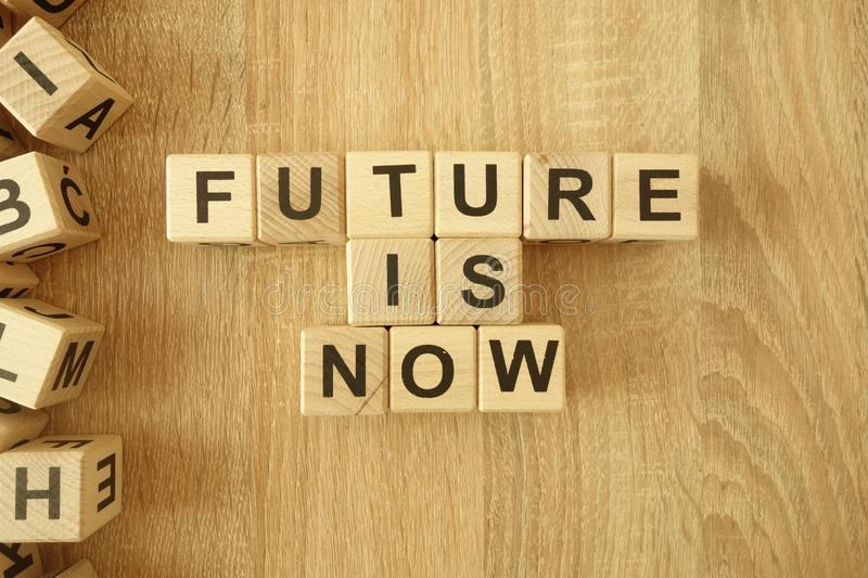 Text future is now from wooden blocks on desk. Background stock images