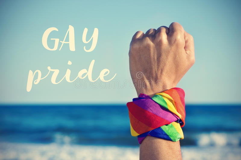 text gay pride and a raised fist with a rainbow-patterned kerchief royalty free stock images