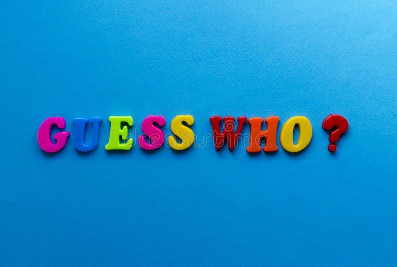 Text gissar vem? från plast- kulöra bokstäver på blå pappers- bakgrund arkivfoton