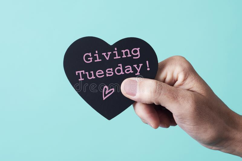 Text giving tuesday in a heart-shaped sign. The hand of a young caucasian man holding a black heart-shaped sign, with the text giving tuesday written in it, on a stock images