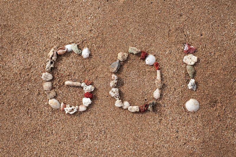 Text Go on sandy beach made from shells. Concept of travel and active lifestyle royalty free stock photography
