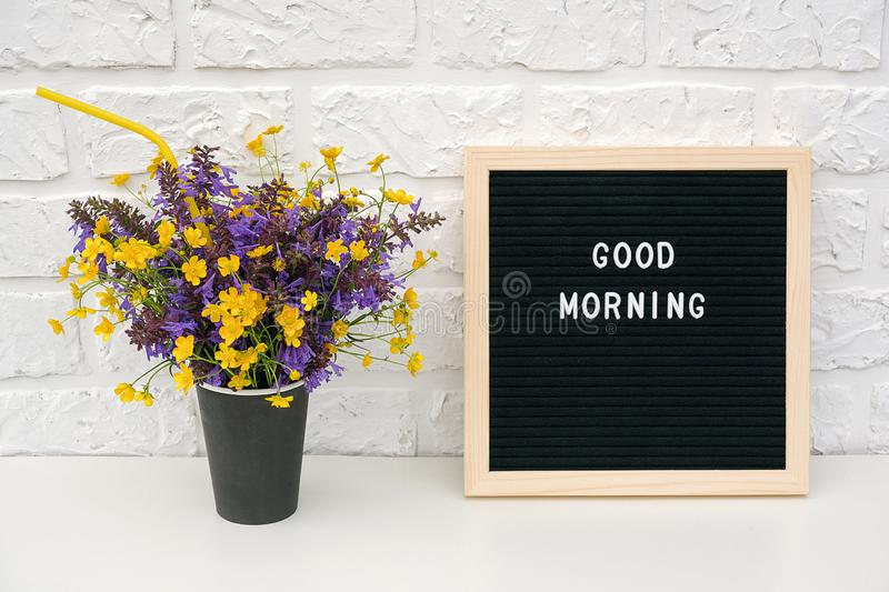 Text Good morning on black letter board and bouquet of colored flowers in black paper coffee cup with cocktail straw on background stock photos