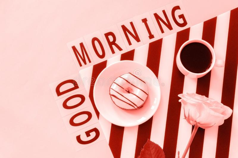 Text Good morning, Coffee, Donut, rose flower on napkin and on pink background. Flat lay Top view Concept stylish workplace stock images