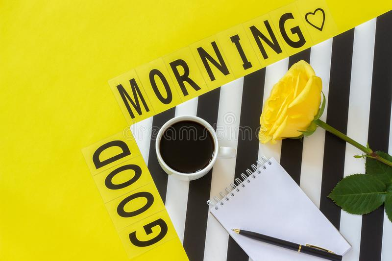 Text Good morning, coffee, yellow rose, notebook for text on stylish black and white napkin on yellow background. Minimal style. Text Good morning, Cup of coffee royalty free stock photography