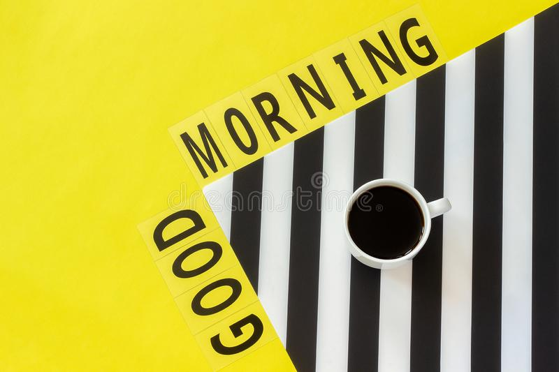 Text Good morning, Cup of coffee on stylish black and white napkin on yellow background. Minimal style. Concept good morning or. Text Good morning and Cup of royalty free stock photo