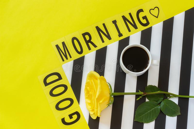 Text Good morning, Cup of coffee and yellow rose on stylish black and white napkin on yellow background. Minimal style. Concept. Good morning or day. Flat lay stock photography