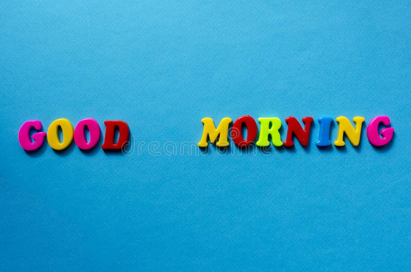 Text good morning from plastic colored letters on blue paper background.  stock photo