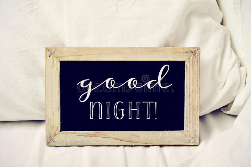 Text good night in a chalkboard on a bed. Closeup of a wooden-framed chalkboard with the text good night written in it, placed on a comfortable bed royalty free stock image