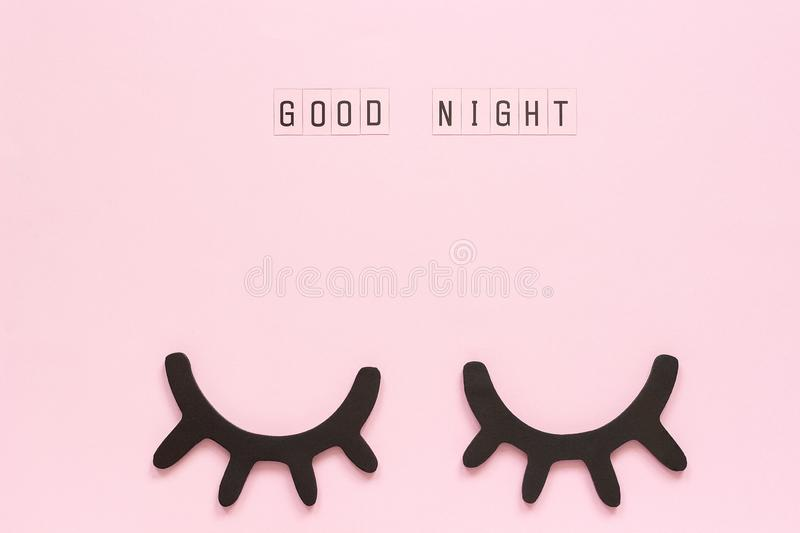 Text Good Night and decorative wooden black eyelashes, closed eyes on pink paper background. Concept Sweet dreams. Greeting card Top view Creative flat lay royalty free stock photo