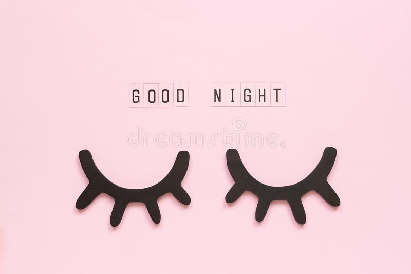 Text Good Night and decorative wooden black eyelashes, closed eyes on pink paper background. Concept Sweet dreams. Greeting card Top view Creative flat lay royalty free stock photos