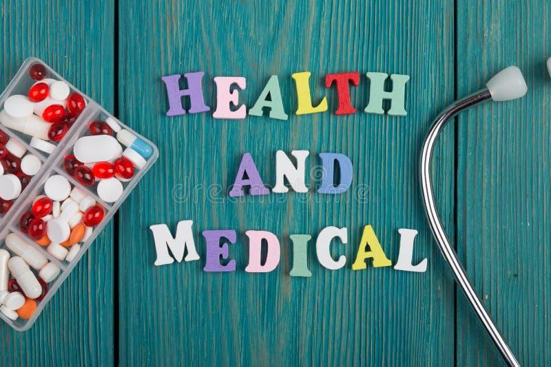 Text & x22; Hälsa och medical& x22; av kulöra träbokstäver, stetoskopet och preventivpillerar arkivfoton