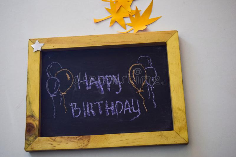Text Happy Birthday on the chalkboard and colorful chalk,autumn leaf origami. White background stock photography