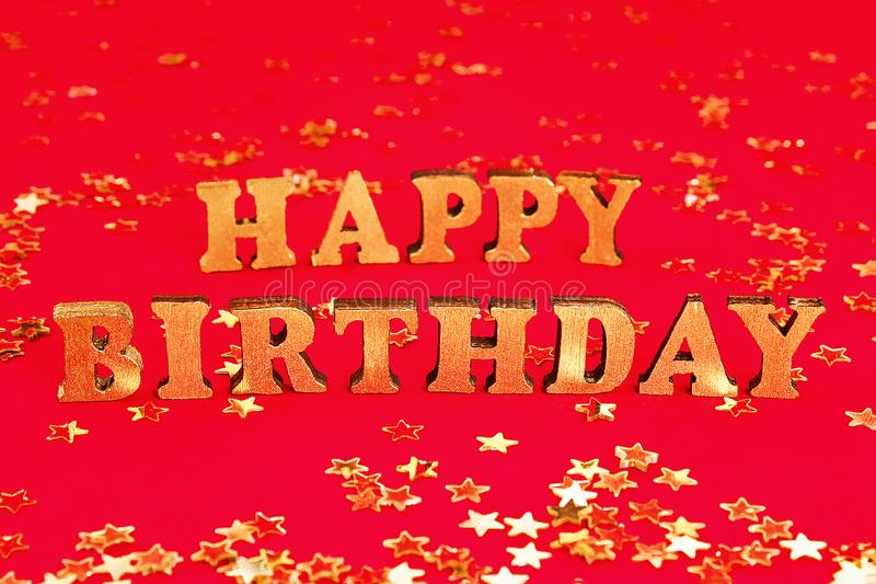 Text Happy birthday laid out of gold letters on beautiful background. Golden stars confetti. Text Happy birthday laid out of gold letters on a beautiful royalty free stock photography