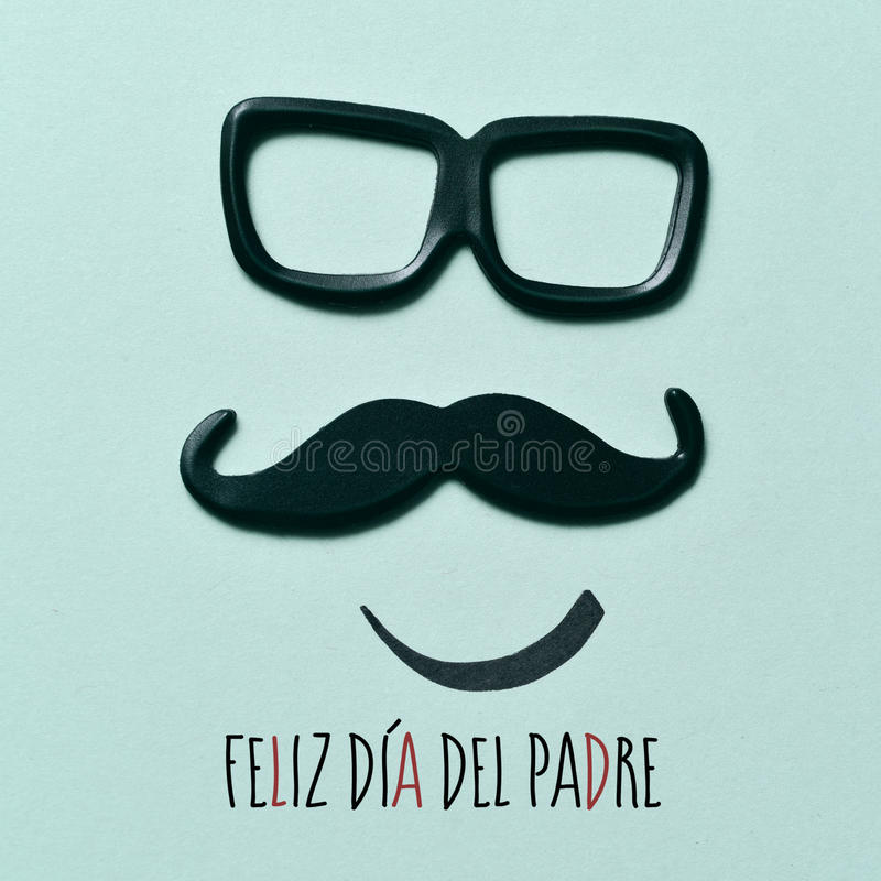 Text happy fathers day in spanish. The text feliz dia del padre, happy fathers day in spanish, and a pair of eyeglasses and a mustache depicting a man face, on a stock photo