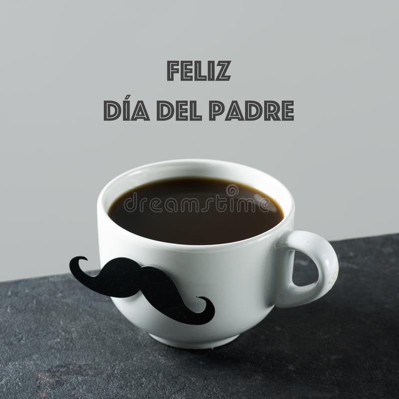 Text happy fathers day in spanish. The text feliz dia del padre, happy fathers day in spanish, and a white ceramic cup with coffee, with a fake mustache attached stock photography