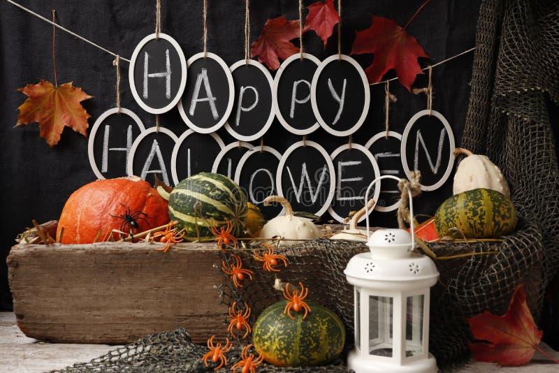 Text `Happy Halloween` and pumpkins. Still life with pumpkins and the text `Happy Halloween` against a white brick wall royalty free stock photos