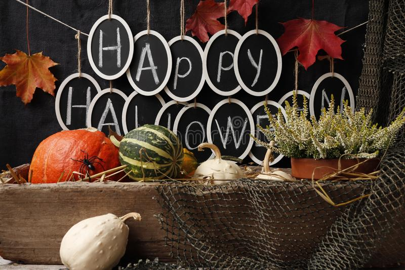 Text `Happy Halloween` and pumpkins. Still life with pumpkins and the text `Happy Halloween` on a dark background stock image