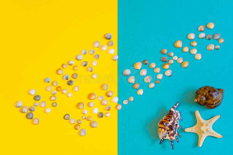 Text Happy Holidays made of small seashells on yellow and blue paper background with sea star and sea shell, symbolizing beach. Text Happy Holidays made of stock images