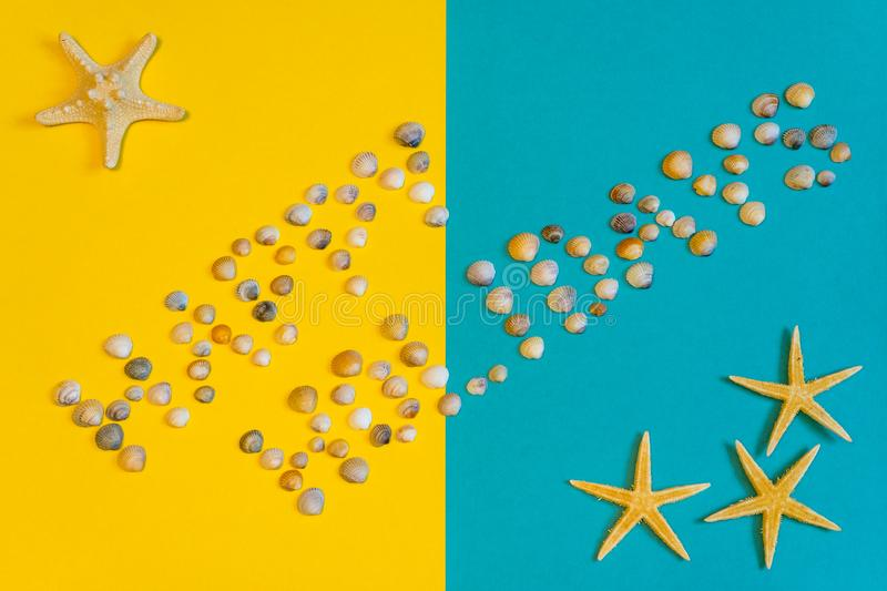 Text Happy Holidays made of small seashells on yellow and blue paper background with sea stars, symbolizing beach. Summer vacation. Text Happy Holidays made of royalty free stock images