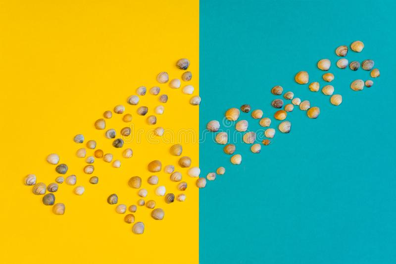 Text Happy Holidays made of small seashells on yellow and blue paper background, symbolizing beach. Summer vacation concept. Text Happy Holidays made of small royalty free stock image