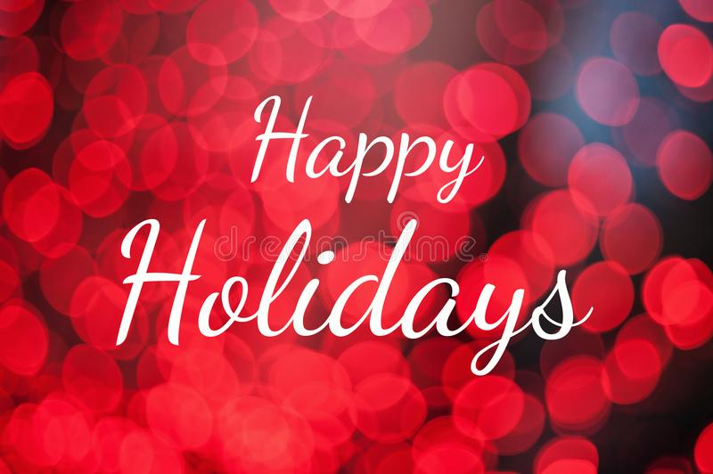 Text Happy Holidays on red lights bokeh background. stock photo