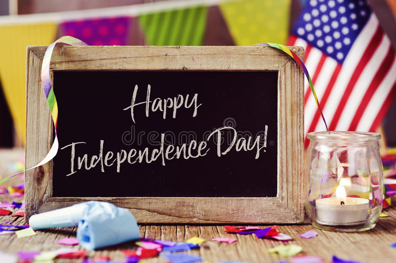 Text happy independence day and american flag. Wooden-framed chalkboard with the text happy independence day written in it and an American flag, placed on a royalty free stock photos
