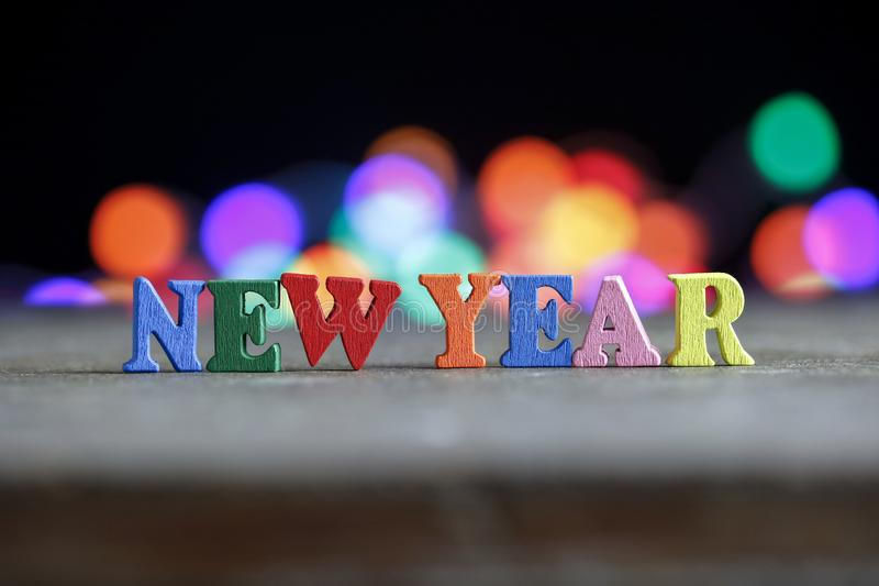 Text Happy New Year of bright multicolored wooden letters. Close-up, dark, colored lights stock photography