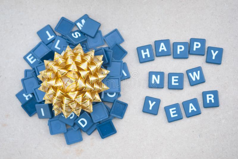 Text happy new years with gold bow against on wooden background. Concept background for happy new year stock photos