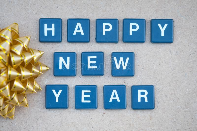 Text happy new years. With gold bow against on wooden background. Concept background for happy new year stock photos