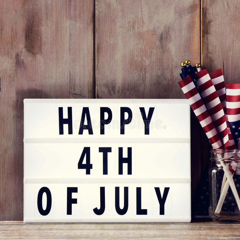 Text happy 4th of july and american flags. A lightbox with the text happy 4th of july and some american flags on a glass jar, on a rustic wooden background royalty free stock photography