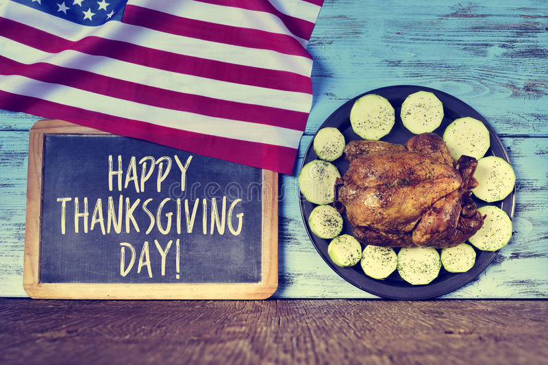 Text happy thanksgiving day and roast turkey. A flag of the United States, a chalkboard with the text happy thanksgiving day and a roast turkey in a tray with stock images
