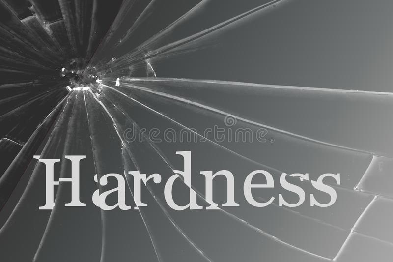 The text Hardness on the broken glass. Background stock photography